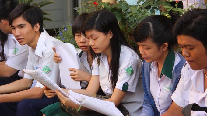 Thí sinh ở TP.HCM tranh thủ xem bài trước khi bước vào phòng thi tốt nghiệp THPT năm 2012 - Ảnh: H.Hương