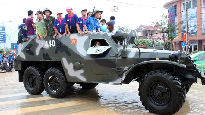 Xe thiết giáp của Bộ chỉ huy quân sự tỉnh Thái Nguyên đưa thí sinh và người nhà qua khu vực ngập nước để đi thi - Ảnh: Thiều Chung